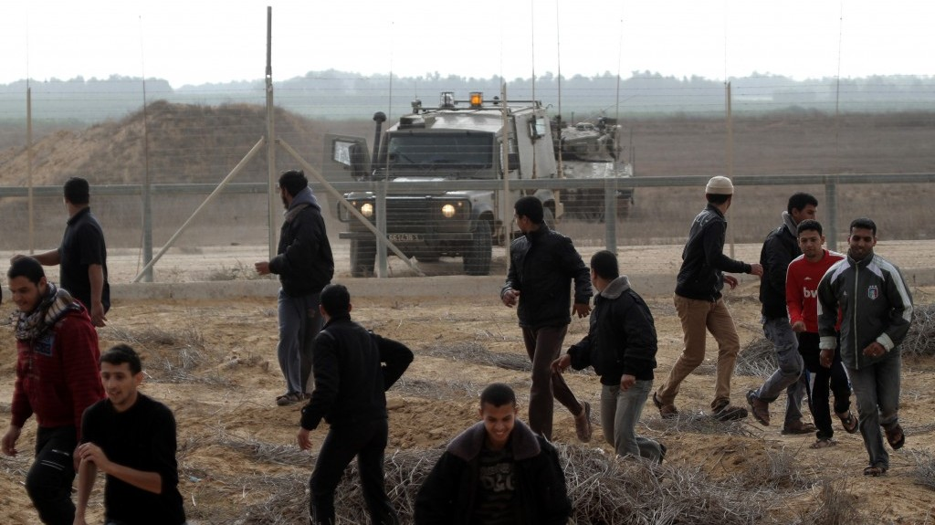 Palestinians stand close to the border fence between Israel and the southern Gaza Strip on November 23, 2012 (photo credit: Abed Rahim Khatib/Flash 90)