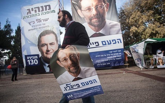 A Likud supporter carries a poster of far-right party member Moshe Feiglin (Uri Lenz/Flash90)