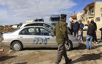 """Graffiti reading """"Gaza"""" is seen spray painted on a car outside the home of an Arab family in the East Jerusalem neighborhood of Shuafat, on November 25 (photo credit: Oren Nahshon/Flash90)"""