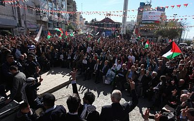 Palestinians wave their national flag during a rally in the West Bank city of Ramallah on Thursday, November 29 (photo credit: Issam Rimawi/Flash90)