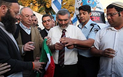 A police officer prevents MK Michael Ben Ari (center) from igniting the Palestinian flag in front of the UN offices in Jerusalem on Thursday, November 29 (photo credit: Yoav Ari Dudkevitch/Flash90)