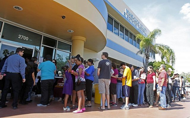 Voters stand in line to pick up their absentee ballots in Doral, Fla., Sunday, Nov. 4, (photo credit: AP/Alan Diaz)