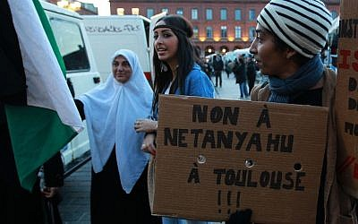 """A French demonstrator holds a placard that reads: """"No Netanyahu in Toulouse"""" as another hold a Palestine flag during a demonstration in Toulouse, southwestern France, Wednesday, Oct. 31, 2012. (photo credit: AP/Bob Edme)"""