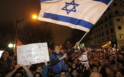 Supporters wave Israeli flags during a Tuesday gathering near the Israeli embassy in Paris. (Francois Mori/AP)