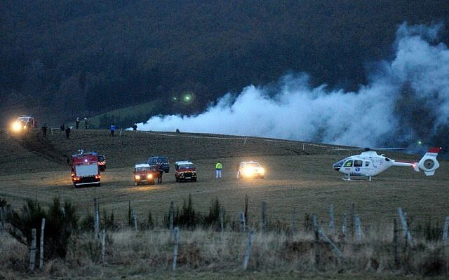 Police, firemen and a medical helicopter near the Algerian military cargo plane crash scene, in Trelans, southern France, on Friday. The plane went down with six people aboard, according to local police. (photo credit: AP Photo/Eva Koord)