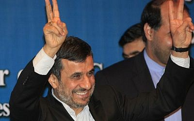 Iranian President Mahmoud Ahmadinejad makes peace gestures on the sidelines of the Bali Democracy Forum in Indonesia last November (photo credit: AP/Dita Alangkara)