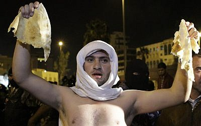 A Jordanian man holds up a piece of bread during a demonstration in Amman following an announcement that Jordan would raise fuel prices, including a 53 percent hike on cooking gas, Tuesday, Nov. 13, 2012. (photo credit: AP/Raad Adayleh)