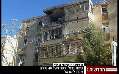 A residential building in Kiryat Malachi suffered a direct hit by a rocket fired from Gaza that killed three people and critically wounded an infant on Thursday, November 15 (screen capture Channel 2 News)