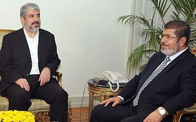 In this image provided by the Egyptian President, Hamas leader Khaled Mashaal, left, meets with Egyptian President Mohammed Morsi at the Presidential Palace in Cairo, Sunday, Nov. 18, 2012 (photo credit: AP)