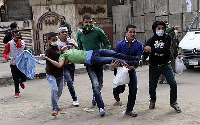 Egyptians carry a protester wounded in clashes with security forces near Tahrir square, where an opposition rally has been called for to voice rejection of President Morsi's seizure of near absolute powers, in Cairo on Tuesday, Nov. 27, 2012 (photo credit: AP/Peter Hartwell)