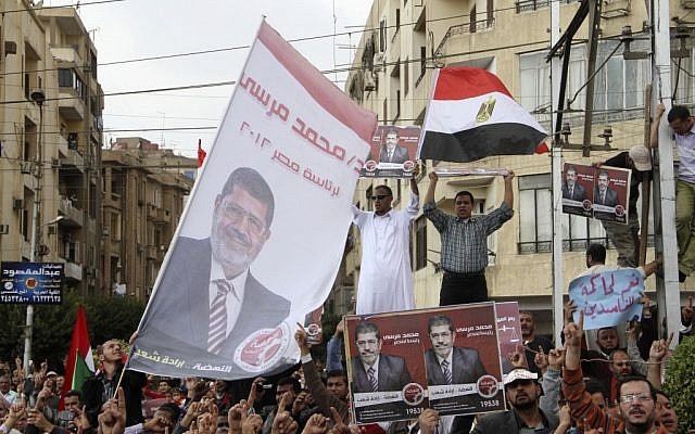 Supporters of Egyptian President Mohammed Morsi chant slogans and wave his campaign posters and a national flag outside the Presidential Palace in Cairo, Egypt, Friday, Nov. 23 (photo credit: AP/Ahmed Gomaa)