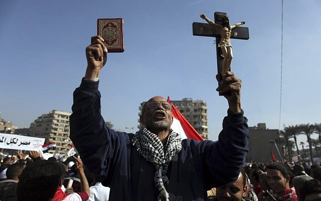 An Egyptian protesters holds a cross and a Quran as he chants anti-Muslim Brotherhood slogans at an opposition rally in Tahrir Square, in Cairo, Egypt, Friday, Nov. 30 (photo credit: AP/Khalil Hamra)