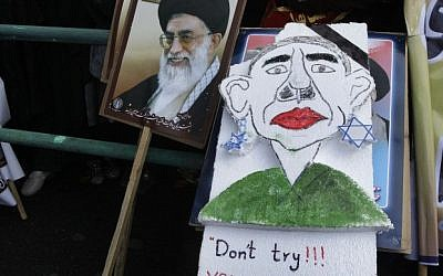 Iranian demonstrators, one holding a caricature of President Barack Obama next to a poster of Iranian Supreme Leader Ayatollah Ali Khamenei, attend an annual state-backed rally in front of the former US Embassy in Tehran, Iran, Friday, Nov. 2, 2012. (photo credit: AP)