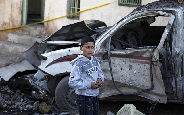 A boy stands next to a destroyed truck at the scene of an explosion in a busy commercial area in Hillah, about 60 miles (95 kilometers) south of Baghdad, Iraq, Thursday, Nov. 29, 2012. (photo credit: Karim Kadim/AP)
