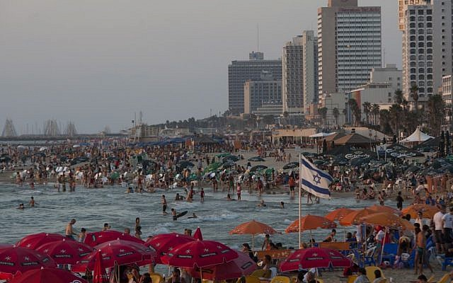 People enjoy the Mediterranean Sea in Tel Aviv, Israel. The freewheeling seaside oasis of Tel Aviv has long served as an escape from the troubles of everyday Israel. Now, it is also the target of rockets fired by Hamas terrorists in the Gaza Strip. (photo credit: AP/Ariel Schalit)