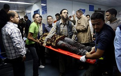 Palestinians bring a wounded man to a hospital in Gaza City, Saturday, Nov. 10 (photo credit: AP/Hatem Moussa)