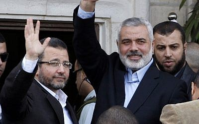 Gaza's Hamas Prime Minister Ismail Haniyeh, right, and Egyptian Prime Minister Hesham Kandil, left, wave to the crowd as they meet in Gaza City on Friday (photo credit: AP/Adel Hana)