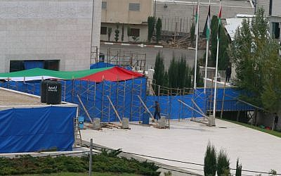 Blue tarp covers the entrance to Yasser Arafat's mausoleum in the West Bank city of Ramallah. The remains of the late Palestinian leader were exhumed from his grave on Tuesday so international forensic experts could search for additional clues to his death (photo credit: AP/Nasser Shiyoukhi)