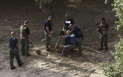 Police sappers remove the remains of a rocket fired by Gazans that landed in Ashkelon in November, 2012. (Photo credit: AP/Tsafrir Abayov)
