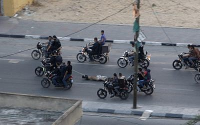 Palestinian gunmen ride motorcycles as they drag the body of a man who was killed as a suspected collaborator with Israel, in Gaza City, November 20, 2012 (photo credit: AP/Hatem Moussa)