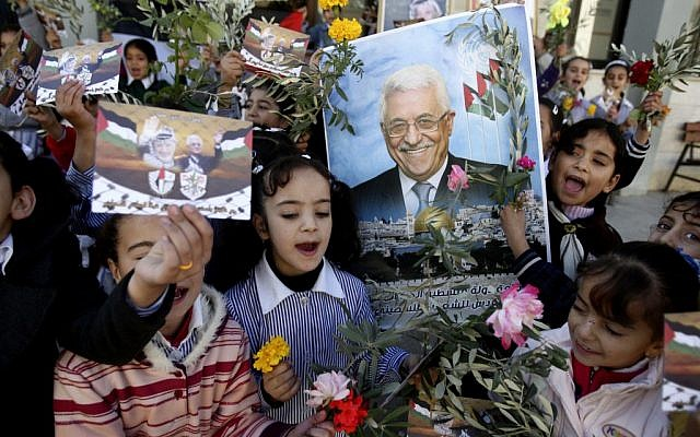 Palestinian schoolgirls hold pictures of President Mahmoud Abbas with Yasser Arafat, flowers and olive branches during a rally supporting the Palestinian UN bid for observer state status, in the West Bank city of Nablus, Wednesday, Nov. 28, 2012. (photo credit:AP/Nasser Ishtayeh)