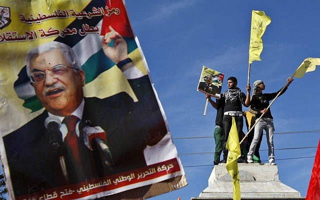 Palestinians wave Fatah flags behind a poster of Palestinian President Mahmoud Abbas during a rally in Gaza City, Thursday, Nov. 29 (photo credit: AP/Adel Hana)