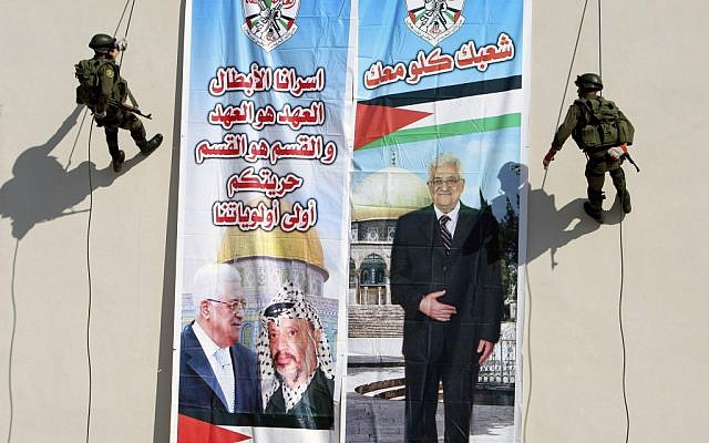 "Palestinian security officers slide down a building next to a banner of PA President Mahmoud Abbas with Yasser Arafat, in the West Bank town of Jenin in 2012. Arabic on the left reads ""our hero prisoners, the covenant is the covenant and the section is the section, your liberty will stay our first priority,"" and right, ""all your people (are) with you.""(photo credit: AP/Mohammed Ballas)"