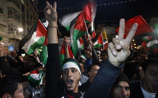 Palestinians celebrate as they watch a screen showing the UN General Assembly votes on a resolution to upgrade the status of the Palestinian Authority to a nonmember observer state, In the West Bank city of Ramallah, Thursday, November 29, 2012. (photo credit: Majdi Mohammed/AP)