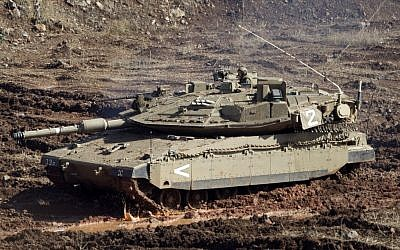 An IDF tank in a firing position on the Golan Heights last year (AP/Ariel Schalit)