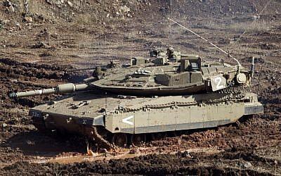 An IDF tank in a firing position on the Golan Heights last year (AP/Ariel Schalit)