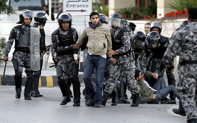 Jordanian policemen detain protesters blocking a main road during a demonstration against a rise in fuel prices in downtown Amman, Wednesday. (photo credit: AP/Raad Adayleh)