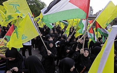 Hezbollah supporters wave Hezbollah and Palestinian flags during a demonstration against the Israeli offensive in Gaza near UN headquarters in Beirut, Lebanon, on Saturday, November 17, 2012 (photo credit: AP Photo/Bilal Hussein)