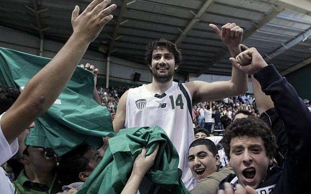 Julian Khazzouh of Sagesse celebrates with fans after their team's win over Riyadi during a basketball game in Ghazir north of Beirut, on November 16, 2012 (photo credit: AP Photo/Bilal Hussein)
