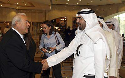 Burhan Ghalioun, leader of the opposition Syrian National Council (SNC), left, shakes hands with one of the attendees during the meeting of the General Assembly of the Syrian National Council in Doha, Qatar, Sunday, November 4, 2012 (photo credit: AP/Osama Faisal)