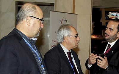 Syrian regime opponent Abdel Baset Seda, center, speaks with one of the participants during the meeting of the General Assembly of the Syrian National Council in Doha, Qatar, on Saturday, November 4, 2012 (photo credit: AP Photo/Osama Faisal)