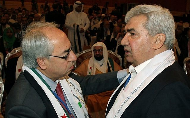 Syrian regime opponent Riad Seif, right, shakes hands with Syrian National Council chief Abdel Basset Seda during the meeting of the General Assembly of the Syrian National Council in Doha, Qatar, on Tuesday, November 6, 2012 (photo credit: AP Photo/Osama Faisal)