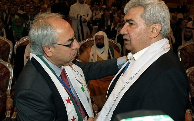 Syrian regime opponent Riad Seif, right, shakes hands with Syrian National Council chief Abdel Basset Seda during the meeting in Doha on Tuesday. (photo credit: AP/Osama Faisal)