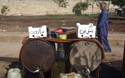 A Syrian man walks behind two containers full of diesel, left, and gasoline, right, for sale in the street in the Syrian village of Atmeh, near the Turkish border with Syria. (AP Photo/Khalil Hamra)