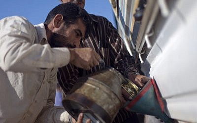 In this Wednesday, Nov. 7, 2012 photo, a Syrian man fuels his car with diesel displayed for sale in the Syrian village of Atmeh. (photo credit: AP)