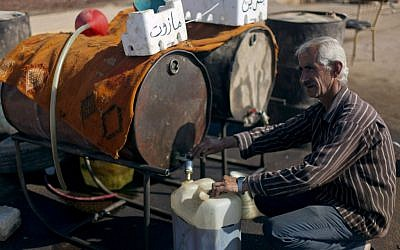 A Syrian man fills a plastic container with diesel fuel from a street vendor in the Syrian village of Atmeh. (photo credit: AP)