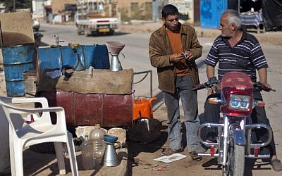 A Syrian man on a motorbike negotiates the price of fuel with a street vendor in the Syrian village of Atmeh, near the Turkish border (AP Photo/ Khalil Hamra)