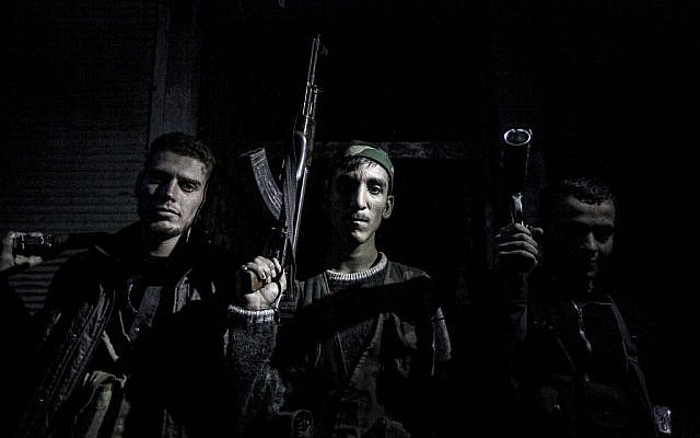 In this file photo from October 2012, Syrian rebel fighters belonging to the Liwa al-Tawhid unit pose after several days of intense clashes in Aleppo (photo credit: AP Photo/Narciso Contreras, File)