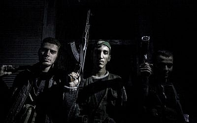 In this Oct. 25, 2012, file photo, Syrian rebel fighters belonging to the Liwa Al Tawhid unit pose for photo in the Karmal Jabl neighborhood after several days of intense clashes between rebel fighters and the Syrian army in Aleppo, Syria (photo credit: AP/Narciso Contreras)