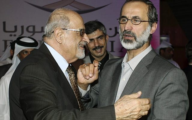 Muslim cleric Mouaz al-Khatib (right) is congratulated after being elected president of the newly formed Syrian National Coalition for Opposition and Revolutionary Forces, in Doha, Qatar, on Sunday, Nov. 11, 2012. (photo credit: Osama Faisal/AP)