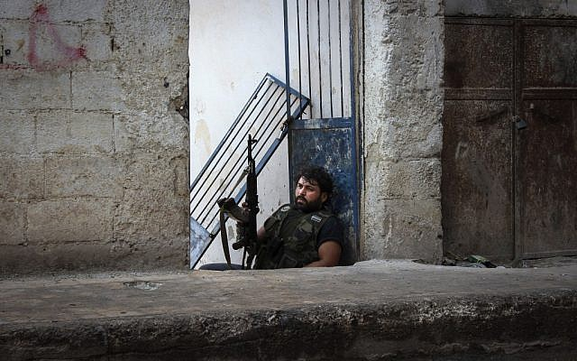 Mustafa, a rebel from the town of Bennish, watches for a sniper firing down a street in the town of Harem, Syria, on Tuesday, Oct. 30, 2012. (photo credit: Mustafa Karali/AP)