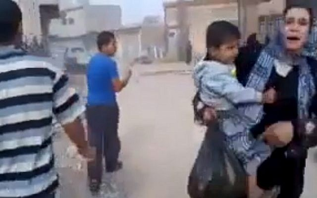 This image taken from video obtained by the Associated Press shows a woman carrying a child running away from the scene of shelling in Qouriyeh, Syria on Friday. (AP/Shaam News Network via AP video)