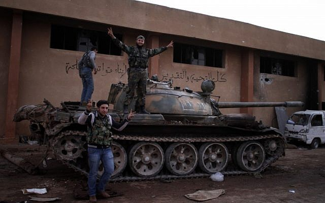 Syrian fighters celebrate their victory on top of a tank they took after storming a military base in Aleppo, Monday, Nov. 19, 2012. (photo credit: Khalil Hamra/AP)