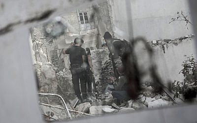 In this illustrative photo, rebel fighters watch over their enemy's position as they prepare themselves to shoot a shoulder-fired rocket towards a Syrian army tank in the Karm al-Jebel neighborhood of Aleppo, Syria. (AP Photo/Narciso Contreras)