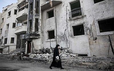 A Syrian woman walks in front of a destroyed hospital on the outskirts of Aleppo, Syria earlier this month (photo credit: AP/Narciso Contreras)