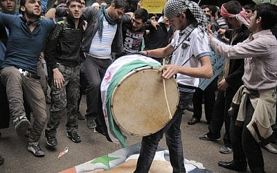 Young Syrians demonstrate against Syrian President Bashar Assad, depicted on the poster beneath the feet of a drummer, in the Bustan al-Qasr neighborhood of Aleppo, Syria, Friday, Nov. 9 (photo credit: AP/Monica G. Prieto)